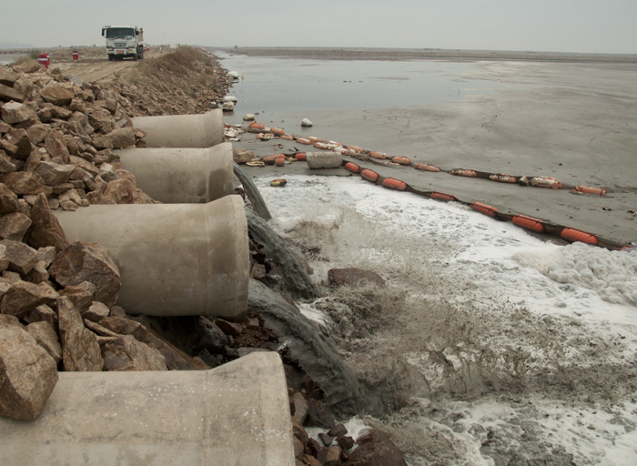 Pipes draining water from other side of dike. A dump truck in the background carries earth for the next dike.