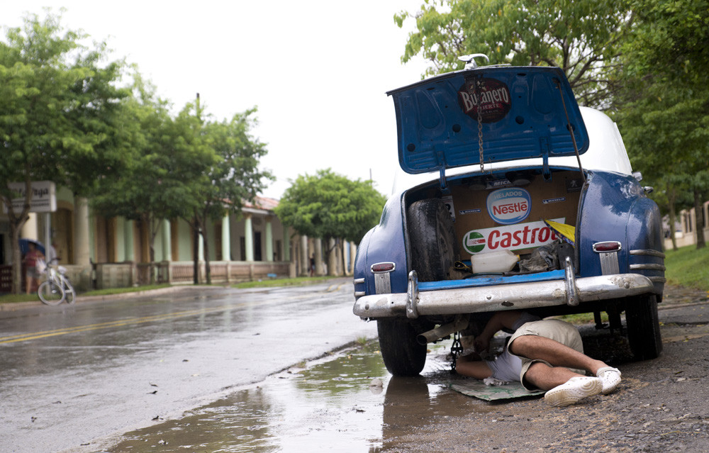 A driver fixing his late 1940's GMC during a downpour in Vinales.